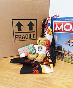 An image of items available in the online shop, in front of a postage box