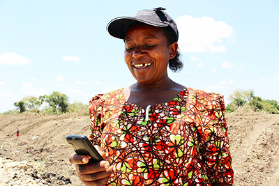 Ghanian woman using mobile phone for online banking
