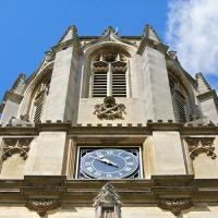 The top of Tom Tower, with a clock face set into it