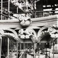 A capital being hoisted in to place