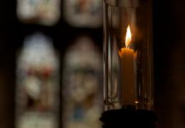 Lit candle with stained glass window in background