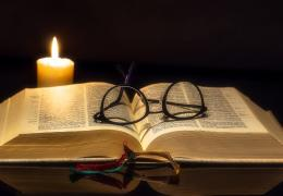 Open Bible with candle and glasses