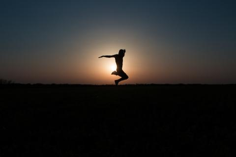 Person jumping with sunset in background
